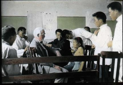 Lantern slide scan of medical clinic being held and patient being treated.