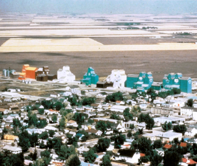 Photograph of prairie town featuring brightly coloured grain elevators