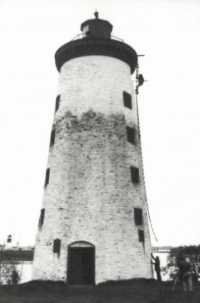 Photograph of restoration work being performed on a lighthouse. One figure is climbing a ladder while another is at the base supporting