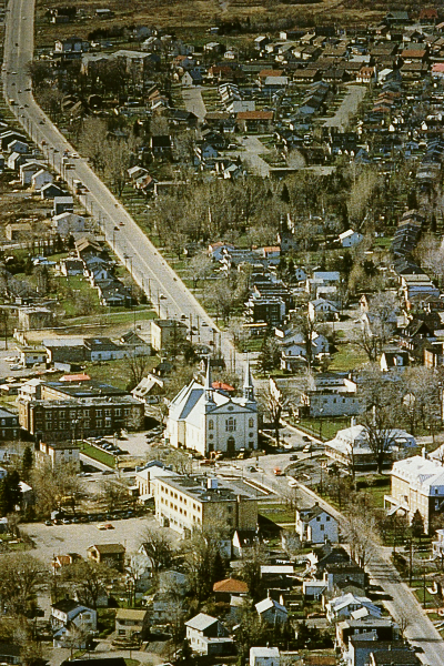 Photograph of Canadian town with highway running through and church at centre.