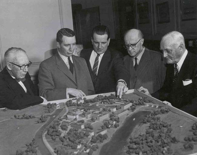 President Claude T. Bissell looks over a scale model plan for the Rideau River Campus with some associates circa 1957