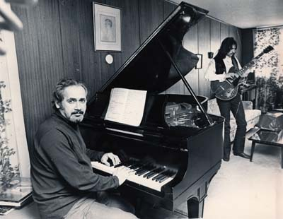 Photograph of Jacob Siskind at piano with guitar player in background