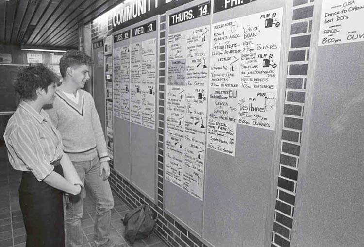 Photograph of students looking at community events board ca. 1990