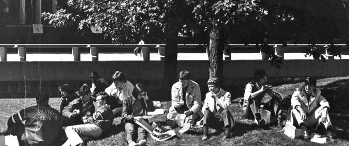 Photographs of students sitting and lying on grass in quadrangle circa 1970