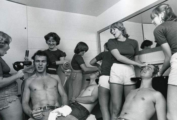 Photograph of female students washing and drying male students' hair