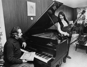 Photograph of Siskind behind piano talking to guitar player