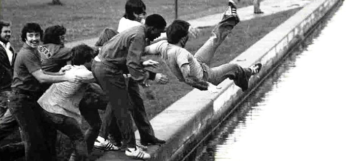 Photograph of a group of students throwing a student into the Rideau Canal