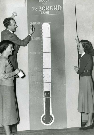 Photograph of the Three Grand Club painting their fundraising goal on large patining of a thermometer