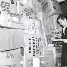 Librarian Hilda Gifford with boxes of books at the Carleton College Library, 1954